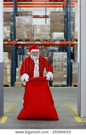 Santa Claus with large red sack full of present standing in the gate to storehouse