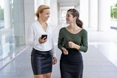 Positive Female Office Employees Enjoying Break Outside Office. Two Business Ladies Walking Outdoors poster