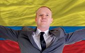 Happy Businessman Because Of Profitable Investment In Columbia Standing Near Flag