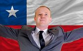 Happy Businessman Because Of Profitable Investment In Chile Standing Near Flag
