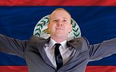Happy Businessman Because Of Profitable Investment In Belize Standing Near Flag
