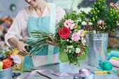 Crop View Of Smiling Florist Snipping Flower Stems poster