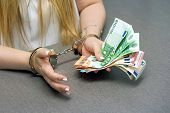 Businesswoman In Office In Handcuffs Holding A Bribe Of Euro Banknote. Close-up Woman Hands In Handc poster