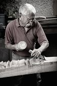foto of woodcarving  - Old woodcarver working with mallet and chiesel - JPG