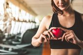 Happy Sport Woman Holding Red Heart In Fitness Gym Club. Medical Cadio Heart Strength Training Lifes poster
