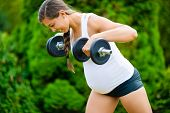 Determined Pregnant Woman Doing Back Workout With Dumbbells In P poster
