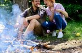 Camping Activity. Couple In Love Camping Forest Eating Roasted Marshmallows. Roasting Marshmallows P poster