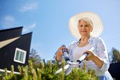 gardening, trimming and people concept - happy senior woman or gardener with hedge trimmer at summer poster