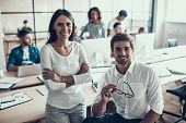 Young Smiling Business People At Work In Office. Portrait Of Young Man And Woman Sitting Next To Gro poster