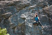The Girl Climbs The Rock. The Climber Is Training To Climb The Rock. A Strong Athlete Overcomes A Di poster