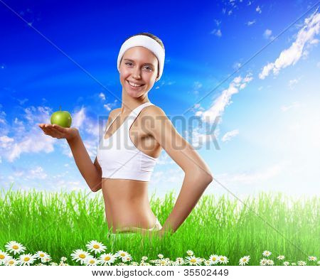 Portrait of a young woman doing sport with a green apple