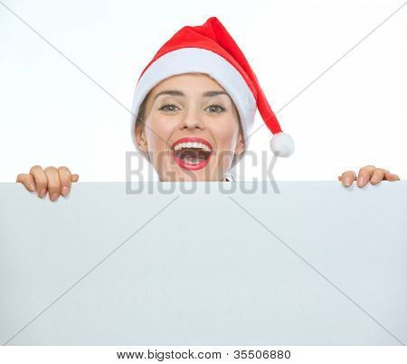 Happy Woman In Christmas Hat Looking Out From Blank Billboard