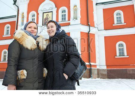 Dos mujeres rusas en ropa de invierno contra el edificio de monasterio ortodoxo. Peregrinación