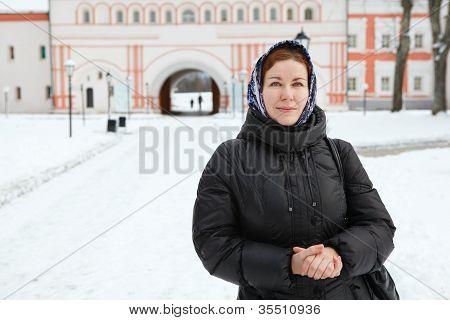 Mujer rusa en ropa de invierno contra el edificio de monasterio ortodoxo. Peregrinación