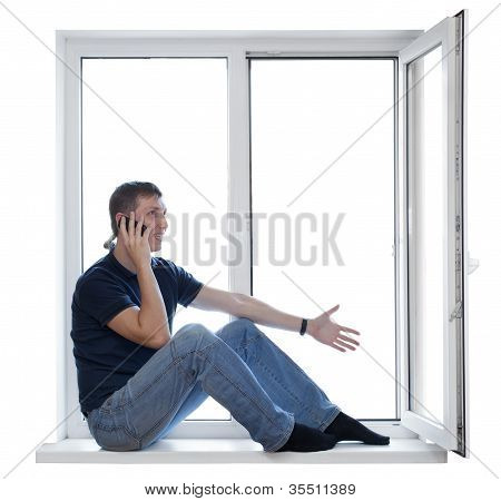 Handsome Man Sitting On Windowsill And Calling On Phone