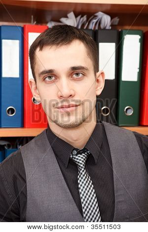 Handsome Male Business Executive Sitting Behind A Bookstand