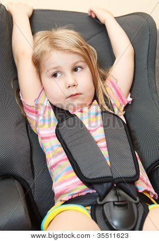 Menina pequena, sentado em uma cadeira com cinto de segurança