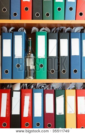 Glass Bottle With Alcohol Hidden Between File Binders On Shelves