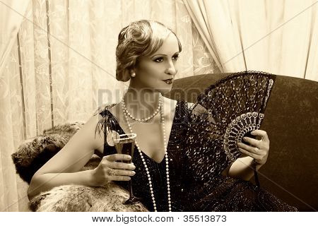 Sepia image of a vintage twenties lady with cocktail and lace fan