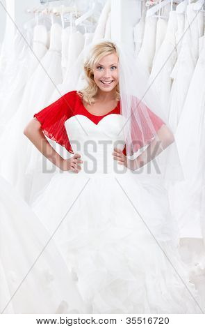 Agitated girl puts a wedding gown to her body, deciding whether it suits for her or not