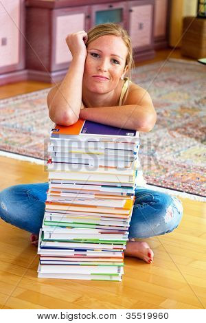a student sits in front of a stack of books to learn the