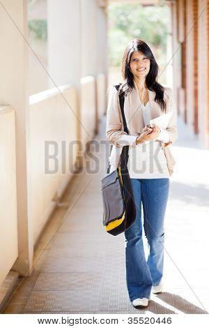 attractive female college student walking down school corridor