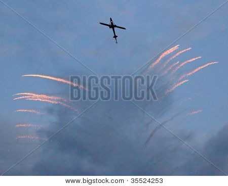 The battle helicopter silhouette with defense (anti missile) rockets against evening sky.