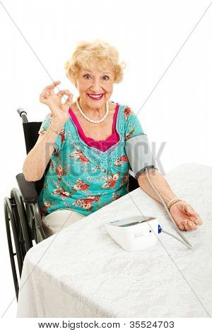 Disabled senior woman in wheelchair taking her own blood pressure at home and giving the okay sign.  White background.