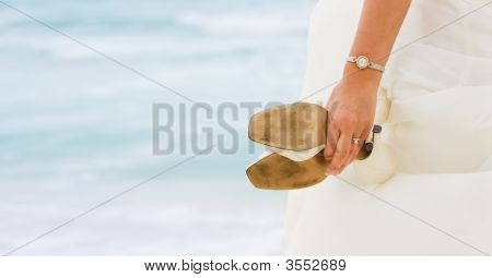 Bride Looking At The Sea With Shoes In Hands