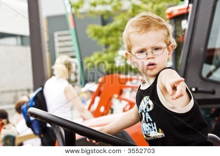 A Little Boy Driving A Tractor (Look Like Is Telling To His Men: