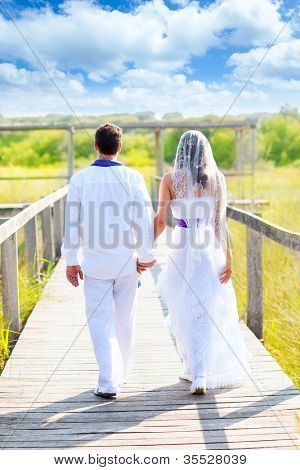 Couple happy in wedding day walking in outdoor rear view