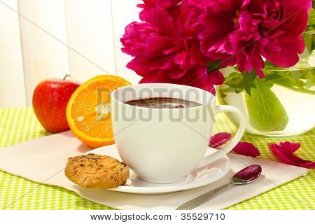 cup hot chocolate, apple, orange, cookies and flowers on table in cafe