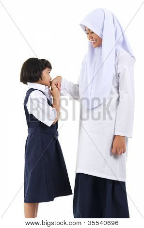 Young Southeast Asian Muslim girl  greeting to her elder sister over white background