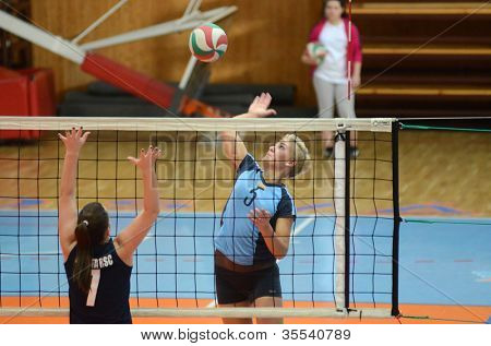 KAPOSVAR, HUNGARY - MARCH 16: Zsofia Horvath (R) in action at the Hungarian Championship volleyball game Kaposvar (blue) vs Palota (deep blue), March 16, 2012 in Kaposvar, Hungary