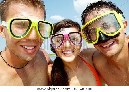 Portrait of three cheerful friends wearing scuba masks and smiling at camera
