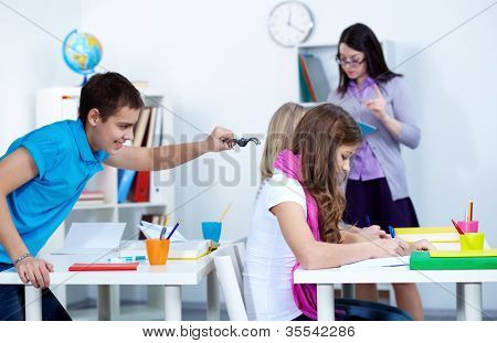 Adolescent guy going to frighten his classmates with black widow at lesson