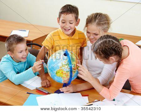 Portrait of cute schoolchildren and teacher looking at globe in classroom