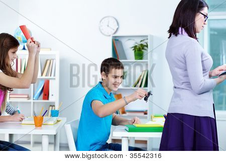 College student holding black spider and going to frighten his teacher at lesson
