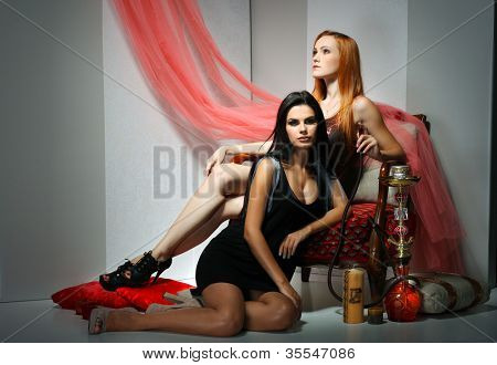 Two beautiful sexual girls in a red arm-chair with a hooka