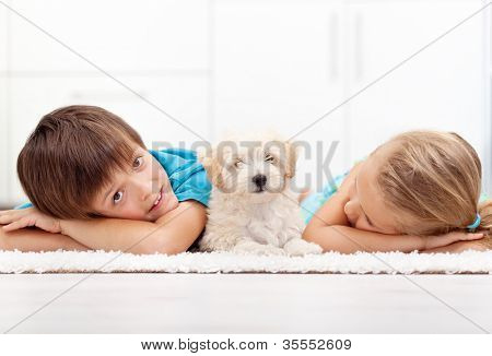 Kids at home with their new pet - a fluffy white dog