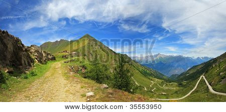 Panoramic view on unpaved road among hills and peaks of Alps, Italy.