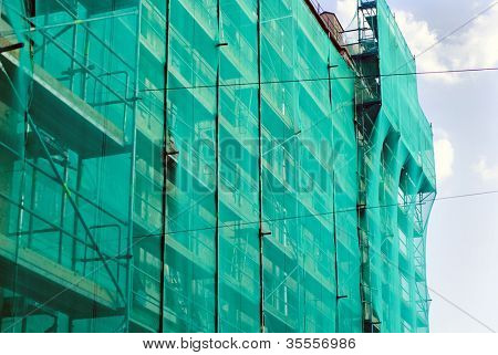 Building is covered with scaffolds and green mesh
