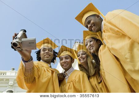 Group of multiethnic friends taking self portrait through camcorder on graduation day