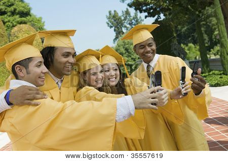 Group of multiethnic friends taking self-portrait through cell phone on graduation day