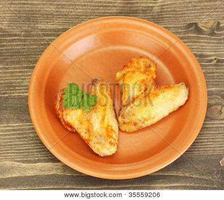roasted chicken wings with parsley in the plate on wooden background close-up