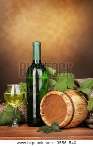 Bottle of great wine with glass and octave on wooden table on brown background