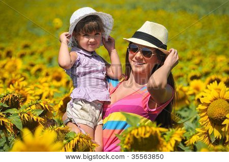 Beautiful woman and child with sunflower in spring field
