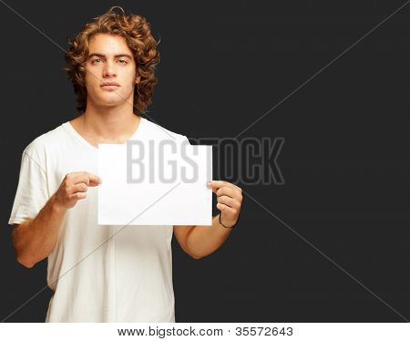 Young Casual Man Holding A Blank Message Isolated On Black Background