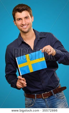 Potrait of a man holding flag on blue background