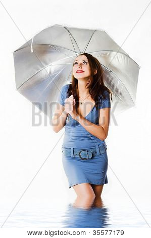 Young women wearing a blue and holding a silver umbrella in water